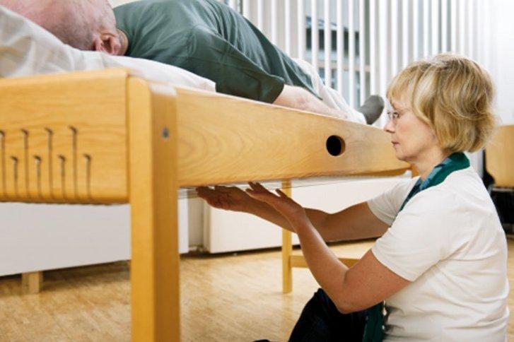 Patientin liegt auf Liege, Therapeutin arbeitet mit ihr